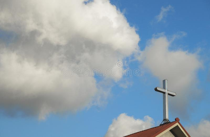 Cross on top of church, with sky and clouds behind. Good for use as background.  stock photos