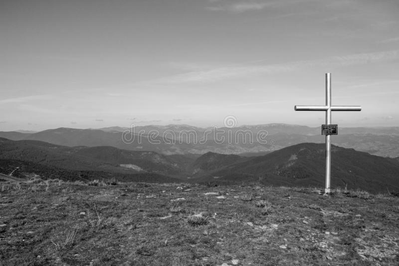 Cross on the top of mountains black and white. Faith and memory sign.Christian religion symbol monochrome. Road to nowhere. stock image
