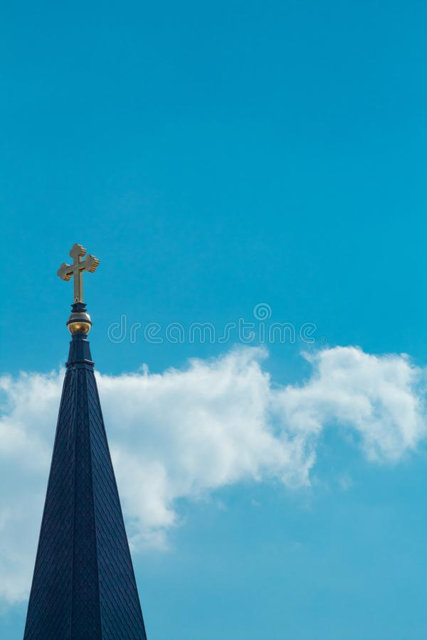 Cross on a Tower. A golden cross atop a peaked tower in a sky of clouds stock images