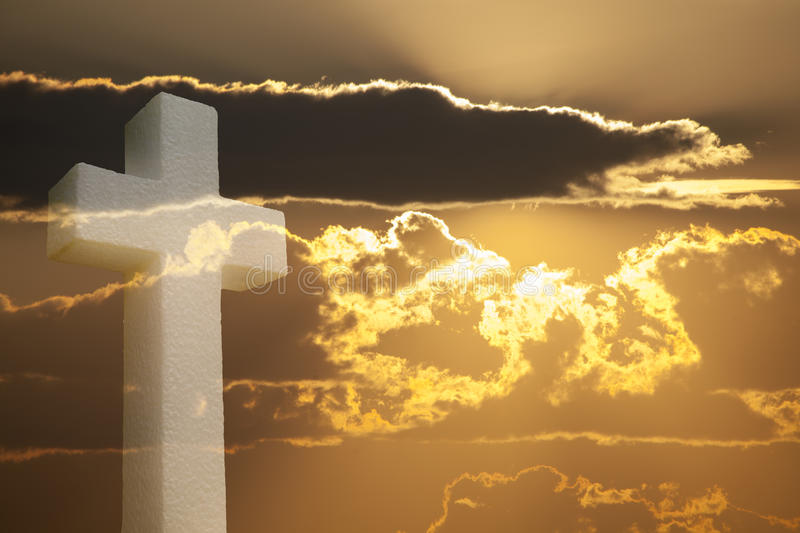 Cross under Bright sunlight shining through clouds royalty free stock photo