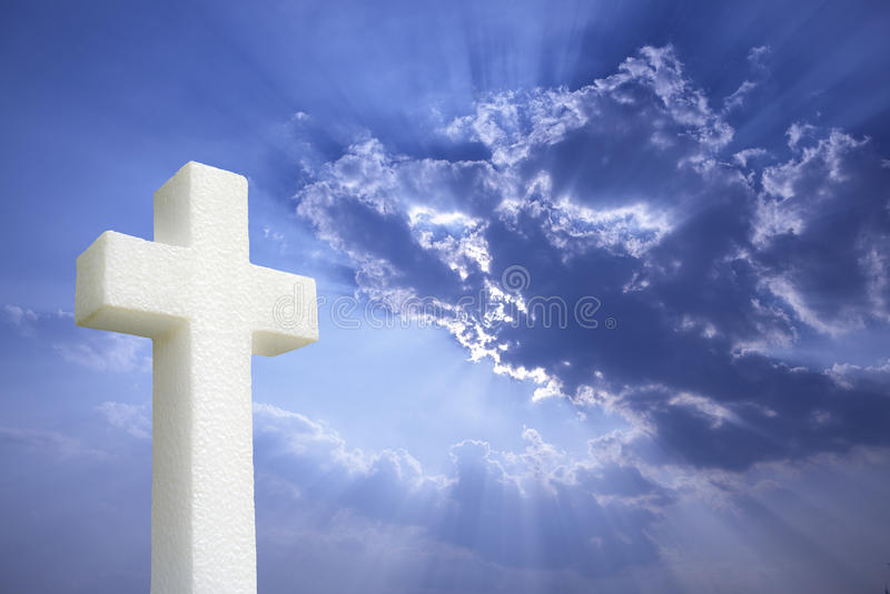 Cross under Bright sunlight shining through clouds royalty free stock photos