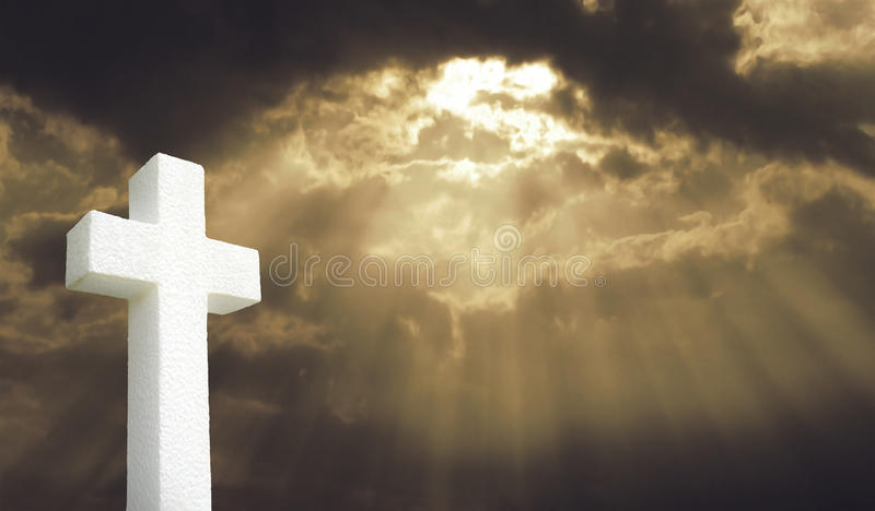 Cross under Bright sunlight shining through clouds royalty free stock images