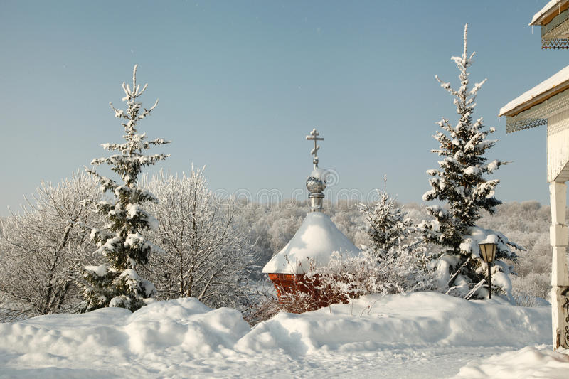 Cross on the winter covered dome amidst snowy fir trees royalty free stock photo