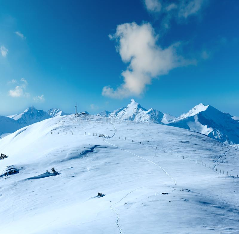 Cross on winter mountain top. Cross on winter mountain Shneeberg top and view Alps peaks behind, Hochkoenig region, Austria royalty free stock image