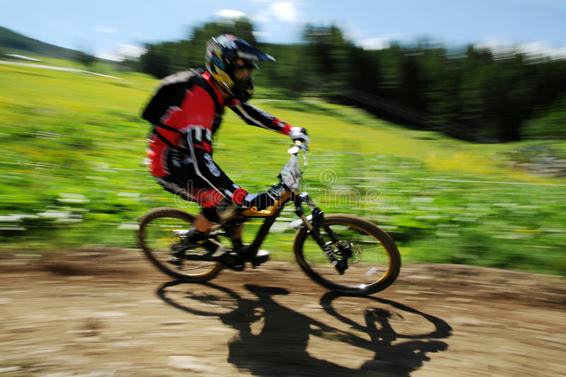 Crosscountry biker. Racing through the green countryside royalty free stock photography