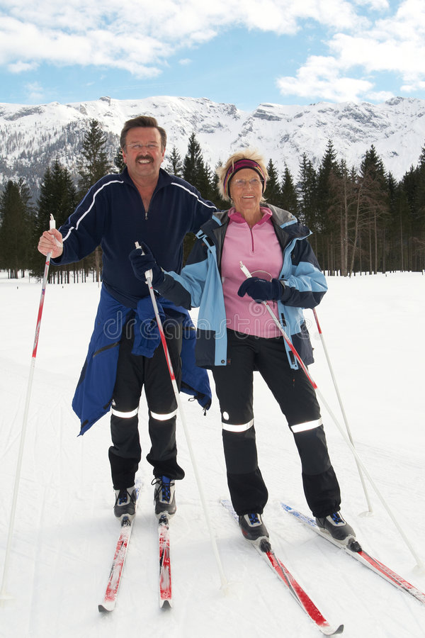 Crosscountry skiing with seniors. A senior couple outdoor in a winter setting. The active couple is about to go crosscountry skiing stock image
