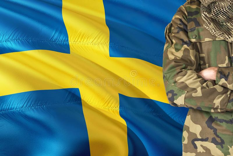 Crossed arms Swedish soldier with national waving flag on background - Sweden Military theme.  stock photography
