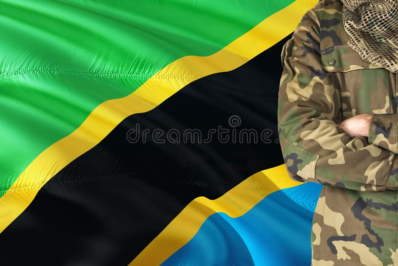 Crossed arms Tanzanian soldier with national waving flag on background - Tanzania Military theme.  stock photo