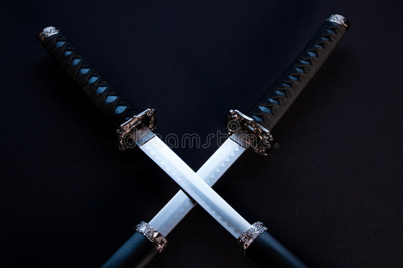 Crossed blades on black background. Two japanese swords with partially drawn blades on dark background stock images
