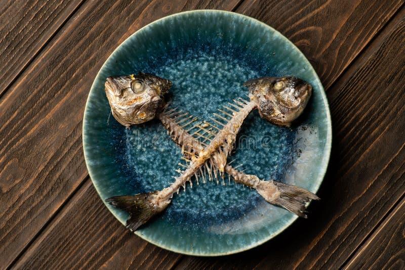 Crossed bones of dorado fish on plate stock images