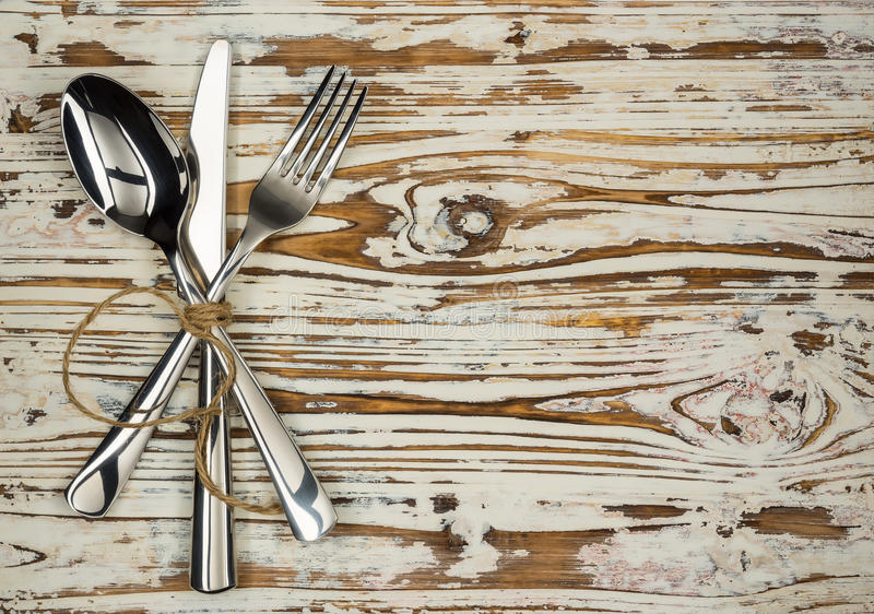 Crossed fork table knife and spoon on old wooden boards royalty free stock photography