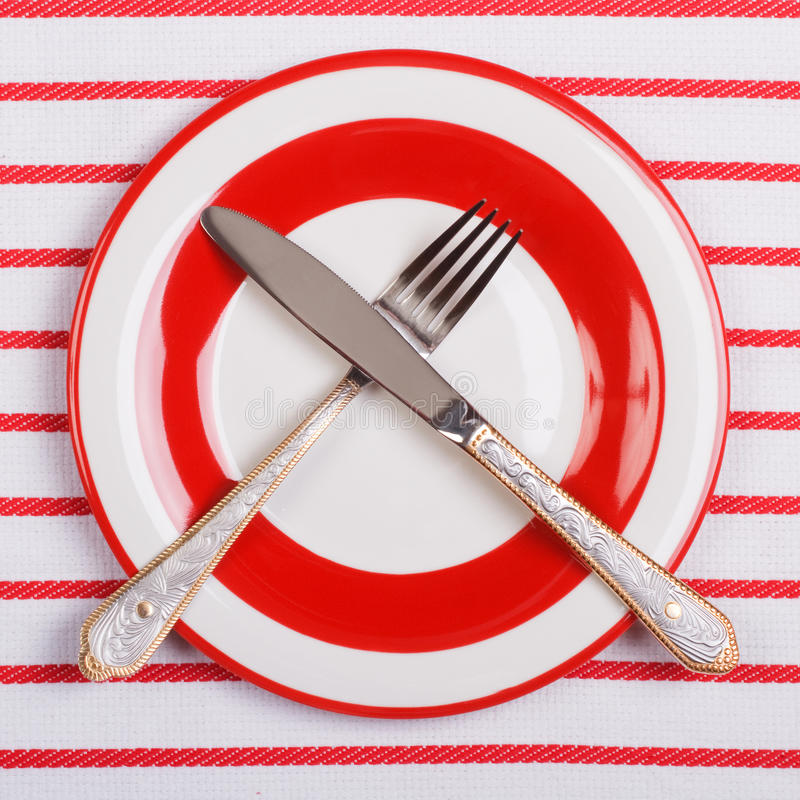 Download Crossed Knife And Fork On A Red Plate On Striped Tablecloth Stock Image - Image: 29927953
