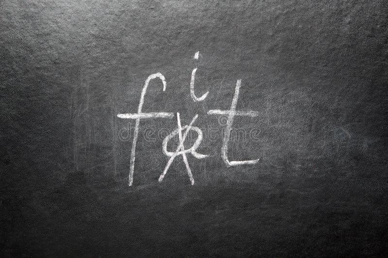 Crossed out word Fat, and written Fit on blackboard, fitness and healthy lifestyle concept. Crossed out word Fat, and written Fit on black blackboard with chalk stock images