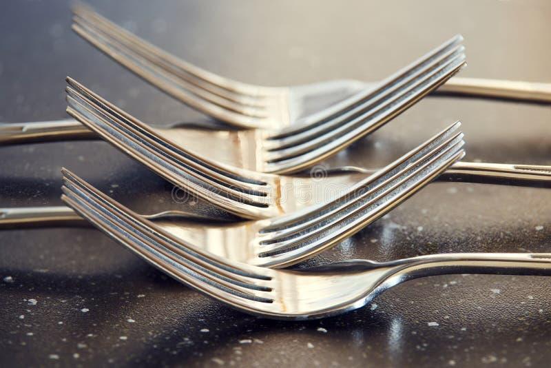 Crossed steel forks on glossy dark table. royalty free stock image