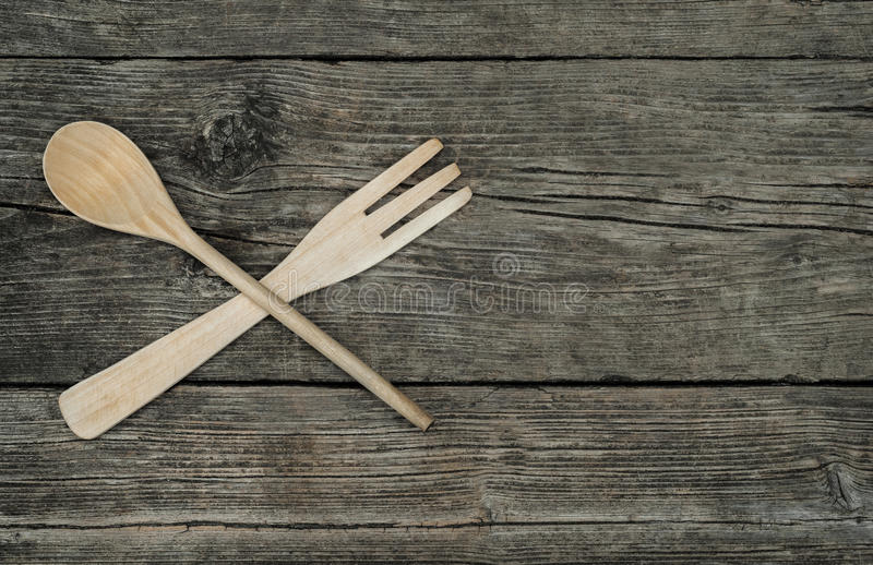 Crossed wooden fork and spoon on rustic background royalty free stock photo