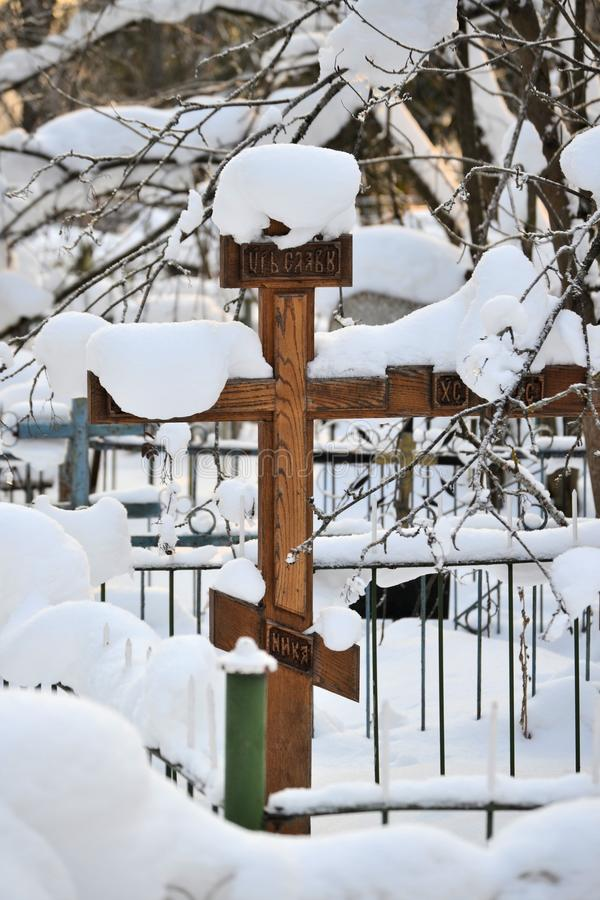 Crosses in a cemetery, monuments of the dead, a cemetery in winter, wreaths, artificial flowers. Russia stock image