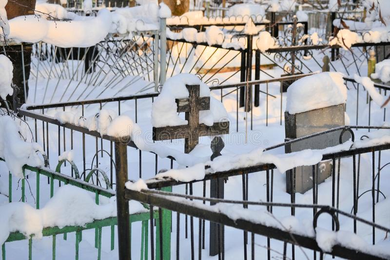 Crosses in a cemetery, monuments of the dead, a cemetery in winter, wreaths, artificial flowers. Russia stock photography