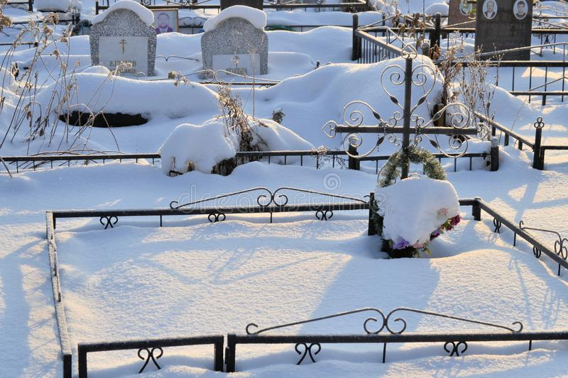 Crosses in a cemetery, monuments of the dead, a cemetery in winter, wreaths, artificial flowers. Russia royalty free stock photo