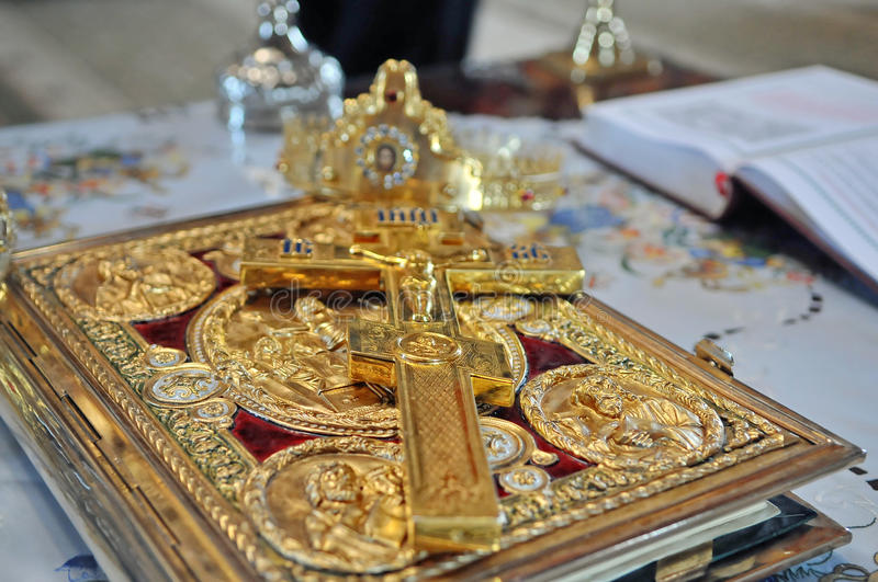Crosses ,rings and crowns of gold on the table in stock photos