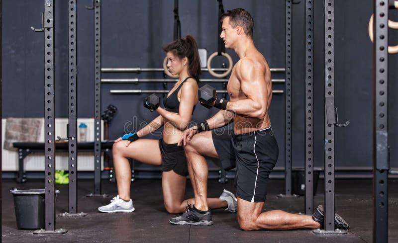Crossfit杠铃训练男人和妇女 在人的焦点前面的 免版税库存照片