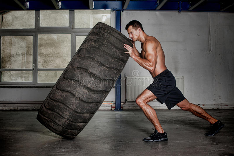 Crossfit训练-翻转轮胎的人 库存图片
