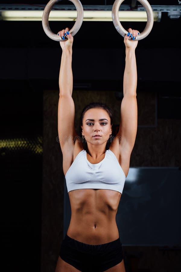 Crossfit Портрет девушки пригонки детенышей мышечной в белой верхней части используя гимнастические кольца стоковые изображения
