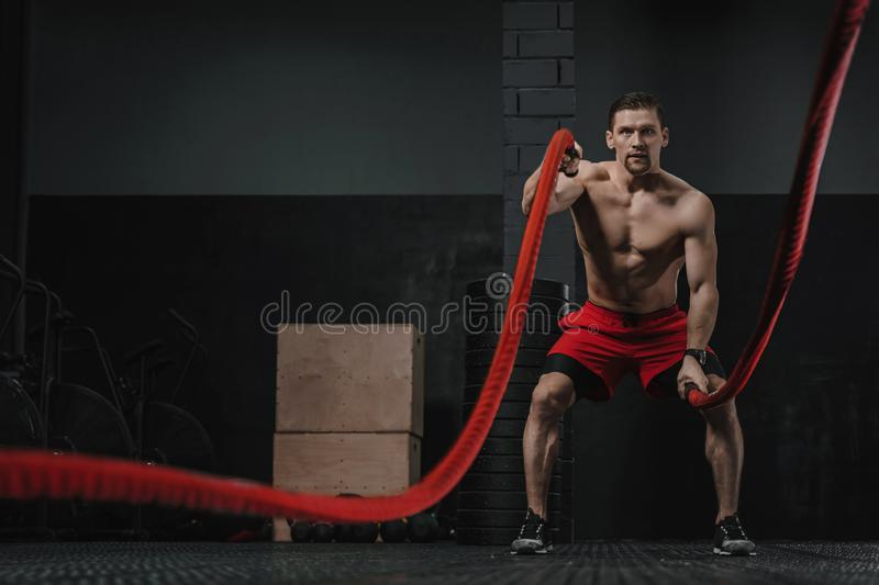 Crossfit athlete doing battle ropes exercise. Young crossfit athlete doing battle ropes exercise at the workout gym. Man training with rope. The sport motivation stock photos