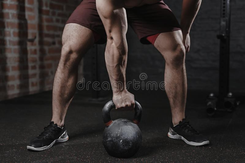 Crossfit athlete exercising with kettlebell at the gym. Handsome man doing functional training. Practicing workout royalty free stock image