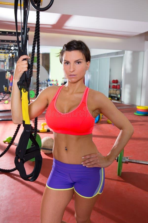 Crossfit-Eignungsfrau, die an der Turnhalle hält trx steht lizenzfreie stockfotos