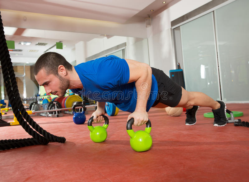 Crossfit fitness man push ups Kettlebells pushup exercise. At gym workout royalty free stock photography