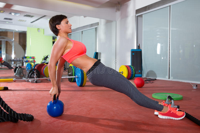Crossfit fitness woman push ups kettlebell pushup exercise. Crossfit fitness woman push ups with Kettlebell rear pushup exercise royalty free stock images