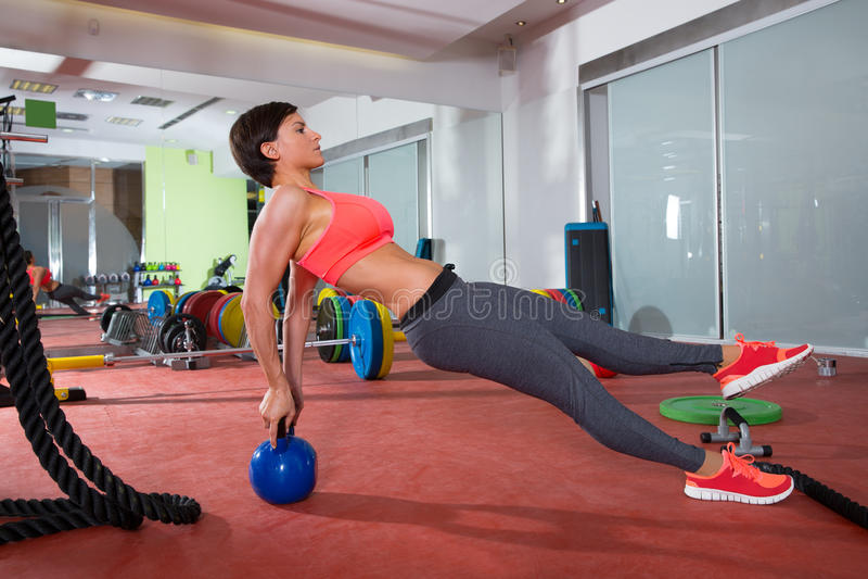 Crossfit fitness woman push ups kettlebell pushup exercise. Crossfit fitness woman push ups with Kettlebell rear pushup exercise stock photo