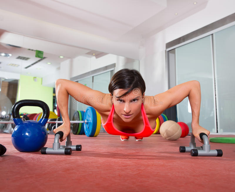 Crossfit fitness woman push ups pushup exercise. Crossfit fitness woman push ups with pushup bars grips exercise royalty free stock photos