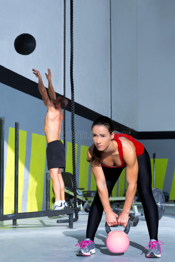 Crossfit gym Kettlebell woman and wall ball man. Crossfit gym Kettlebell woman and jumping wall ball man workout at gym stock photo