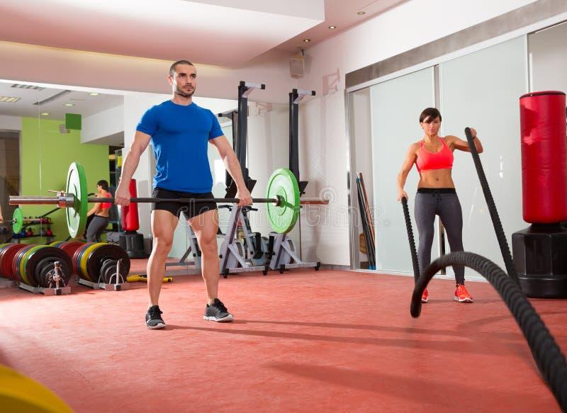 Crossfit gym weight lifting bar man woman battling ropes royalty free stock image