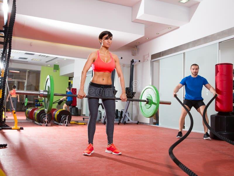 Crossfit gym weight lifting bar woman man battling ropes stock images