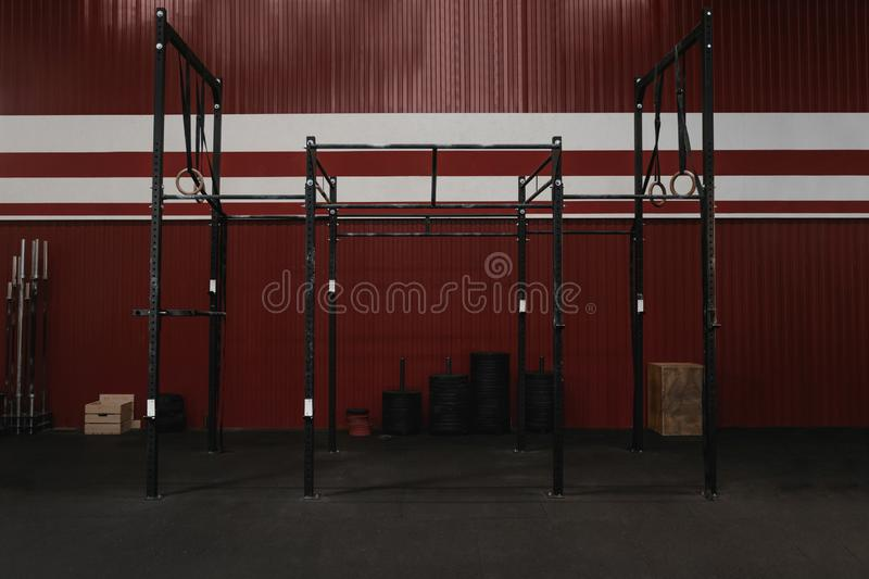 Crossfit gym with workout equipment. Horizontal bars, gymnastic rings. Garage red color gym interior royalty free stock photos