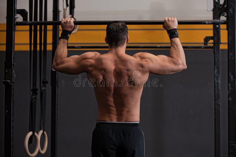 Crossfit handtag upp konditionövningen - som är tillbaka av en man arkivfoton