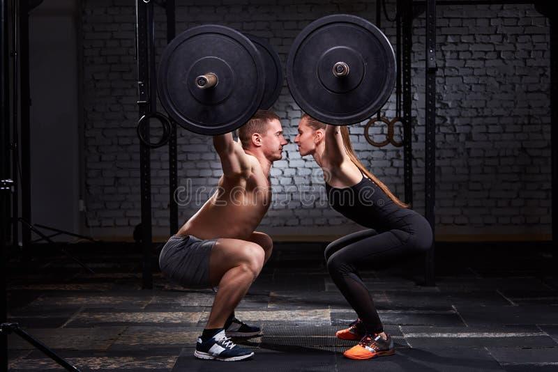 Crossfit lyftande stång av kvinnan och mannen i gruppgenomkörare mot tegelstenväggen arkivfoton