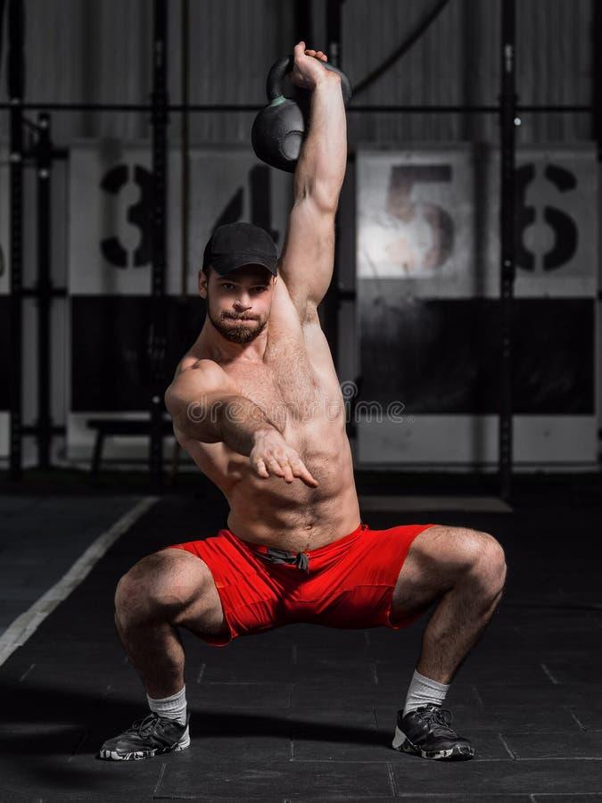 CrossFit opleiding Geschiktheidsmens die een gewichtheffen doen door liftin stock fotografie