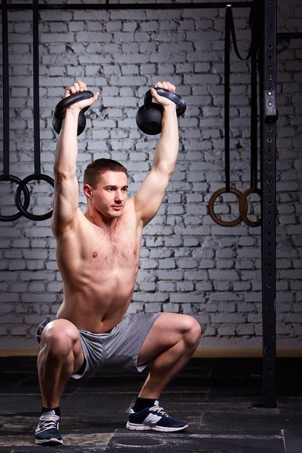 CrossFit opleiding Geschiktheidsmens in grijze borrels die een gewichtheffen doen door op te heffen kettlebells stock afbeeldingen
