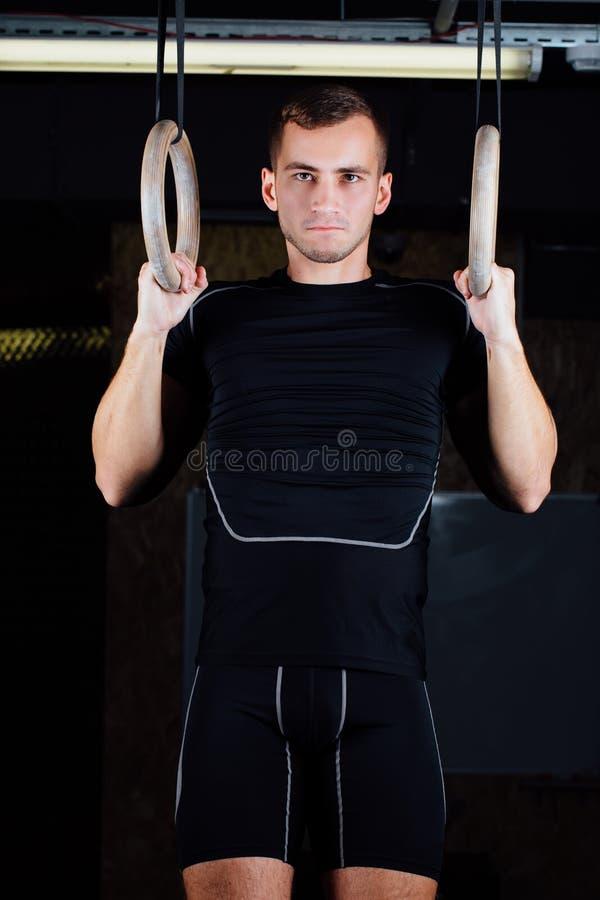 Crossfit Portrait de l'homme musculaire d'ajustement de jeunes employant les anneaux gymnastiques images libres de droits