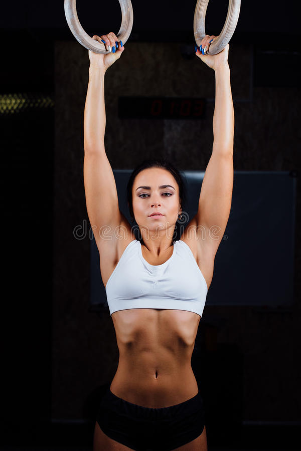 Crossfit. Portrait of young fit muscular girl in white top using gymnastic rings royalty free stock images
