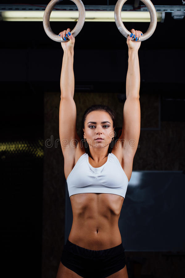 Crossfit. Portrait of young fit muscular girl in white top using gymnastic rings stock images