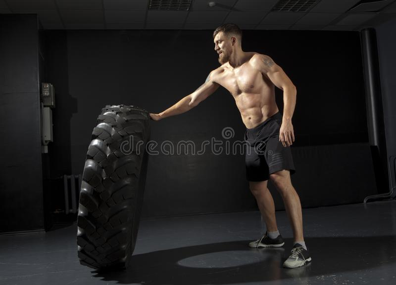 Crossfit training - man flipping tire stock images