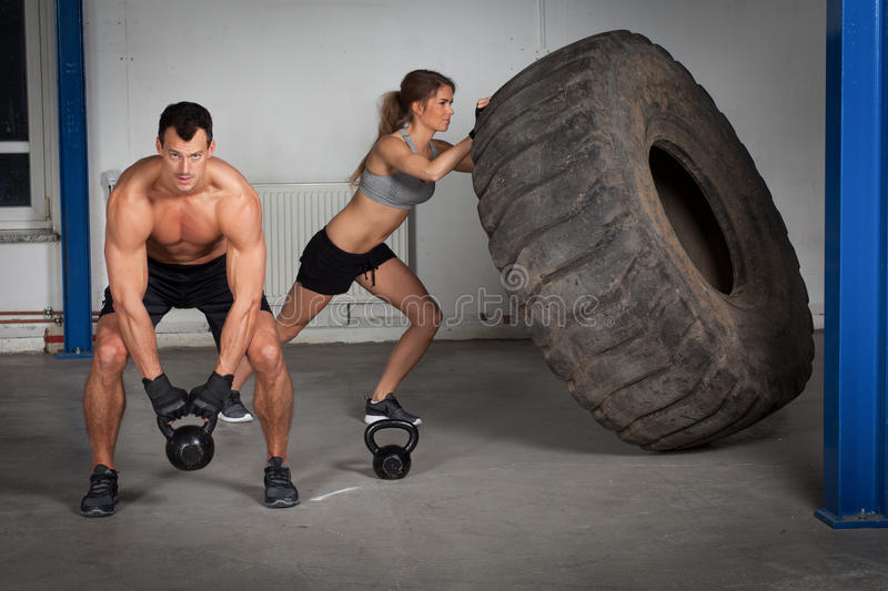 Crossfit training - woman flipping tire stock images