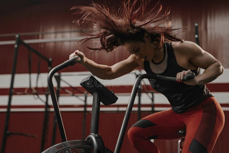 Crossfit woman doing intense cardio training on exercise bike. Her hair is flying from the air flow. Copy space stock photo