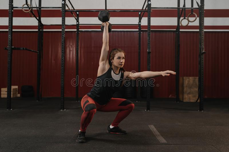 Crossfit woman doing overhead dumbbell squats at the gym. Female athlete practicing workout with weights royalty free stock images
