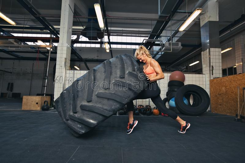 Crossfit woman flipping a huge tire at gym. Fit female athlete working out with a huge tire, turning and flipping in the gym. Crossfit woman exercising with big royalty free stock image