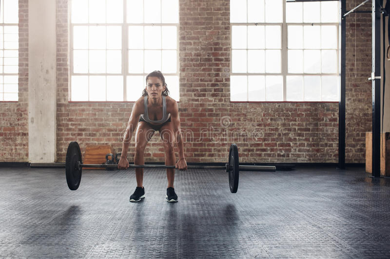Crossfit woman lifting heavy weights in gym royalty free stock images